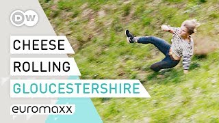 It's a cheesy tradition held annually near the town of gloucester, uk. hundreds volunteers risk their health to catch up with cheese rolling down stee...