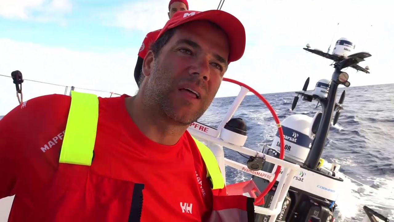 Pablo, in the cockpit, talks in Spanish about the leg so far. Dongfeng a half mile ahead; rest of the fleet behind. He talks in Spanish about what's coming up in the leg. Then he does it all again in English. In theory it's a leg without too many maneuvers. Will be a lot of cloud activity and stalls, lots of peels. Have to keep their focus if they're going to win this leg. Other boats will be close by. Speed of the boat is key in this kind of leg. You want to gain meter by meter. You get a small advantage, and then you can use that to get in the right position with the clouds. Shot of sunset with fleet close behind them. Rob and Tamara stacking on the foredeck. Rob on the helm with other boats behind them. Dongfeng crossing on starboard a half mile ahead of them. Shifting the stack to leeward in preparation for tacking. We see the tack from the cabin, looking aft. Xabi calling jib trim. Blair and Neti on the bow. Lowering the J1.