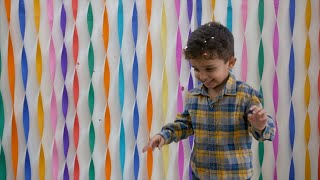 Happy little boy dancing under falling confetti at a birthday party