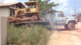 Caminhão velho carregando trator esteira