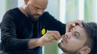 Closeup shot of a barber shaving beard of a man in a salon