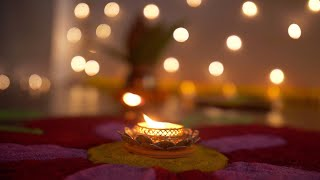 Bokeh shot of a glowing oil lamp on colorful rangoli on Diwali - the festival of India