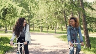 Dolly Shot of Happy Young Women Cheerful Students Riding Bicycles in City Park, Talking and