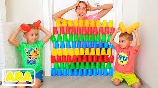 فلاد و نيكيتا ووالدتهم يلعبون بالأكواب الملونة