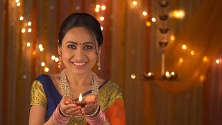 Traditional woman belonging to Hindu family lighting diya and bringing up in front of the camera - Diwali Invitation