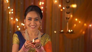 Traditional woman belonging to Hindu family lighting diya and bringing up in front of the camera - Diwali Invitation