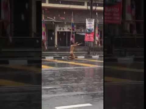 Man walks naked in pouring rain outside Penang market