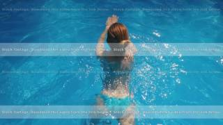 blonde dressed in light blue swimsuit is swimming in a pool, top view