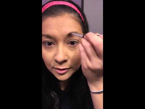 Filling in your brows with loose mineral pigment powder