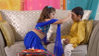 Raksha Bandhan - Cute Indian girl putting tilak on her brother's forehead for Rakhi festival