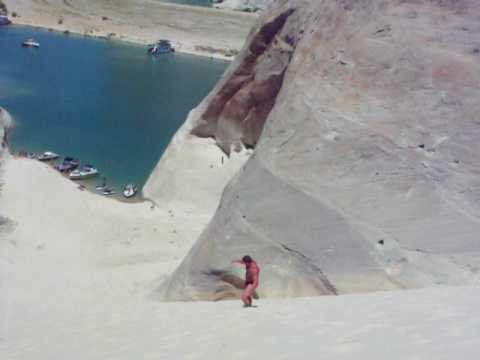 Big buff dude doing cartwheels down a sand hill in a speedo at Lake Powell