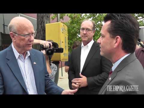 Pat Roberts & Milton Wolf speak on the street in Emporia