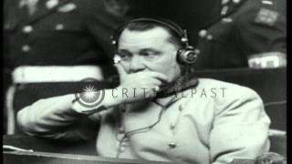 German war prisoners sit, converse and speak on microphone during war crime trial...HD Stock Footage