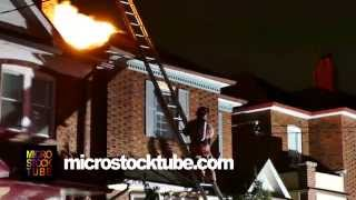 Fire fighter stepping halfway on a ladder leaning on house on fire - Commercial licensing