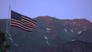 United States flag waving in front of a mountain.