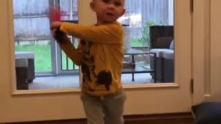 kid practices baseball stance at home - 1016697
