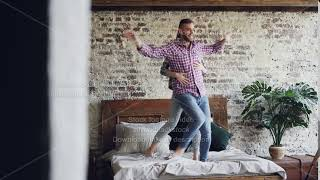 Funny young couple is dancing on bed having fun in loft style bedroom and laughing. Happy people