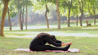"A girl performing ""Paschimottanasana"" move in a park while exercising yoga"