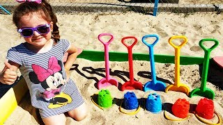 Маша играет в песочнице с  ведрам и лопатками для детей