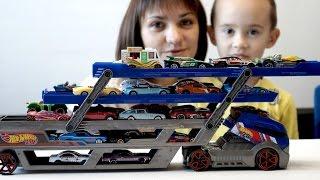 Игрушечный Автовоз и очень много машинок. Дети распаковывают игрушки Hot Wheels