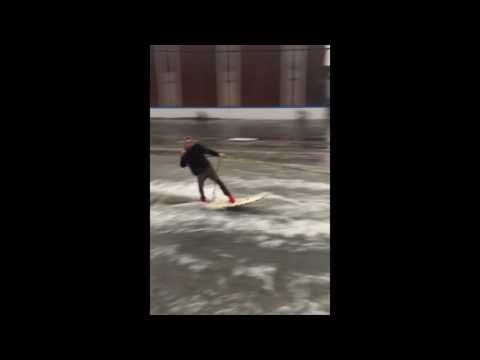 Man rides surfboard down flooded street in Los Angeles