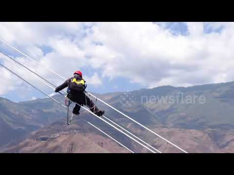 Chinese electricians conduct maintenance on power lines 400 metres above river