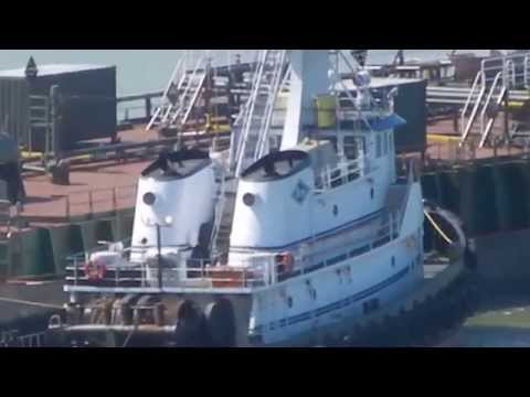 Tugs working together to assist a tank barge