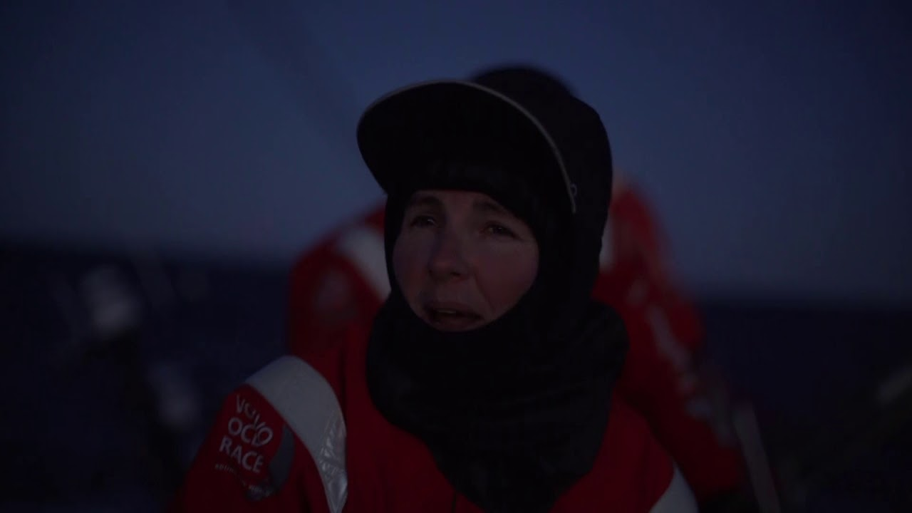 Jena trims as they sail upwind toward the Norway turning mark. Hoisting the A3 in preparation for the rounding. Other boats already having rounded. Stacey: Arriving at the first mark on the coast of Norway. It's midnight and the sun's coming up. The cherry red boats have just rounded, and Akzo is just behind us. SiFi points out the buoy. Stacking to leeward in preparation for the rounding. SiFi calls the time to the tack: 1:10. Charlie calls the tack from the helm. Buoy wiht the moon behind it. Charlie calls the deploy. Sailing downwind with the sunrise behind them. TTToP on their weather quarter tacking for the mark. Tony fiddling with the outrigger. SiFi laughs about the midsummer night, relates the events of the beat up. Happy to have got out in third, and slightly faster than the boats ahead at the moment, so it's all good.