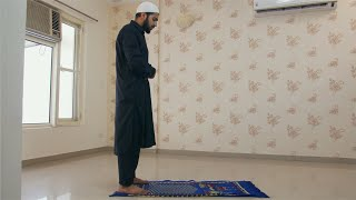 Muslim man wearing kufi prostrating and worshiping Allah on the carpet at home