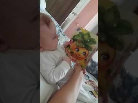 Младенец с эмоцией читает книгу