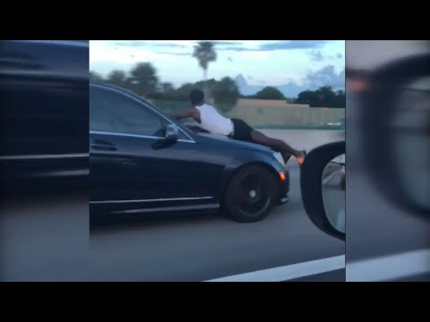 Driver records man riding on hood of car down I-95 in Miami