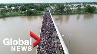 Drone shows migrant caravan on border bridge heading for Mexico