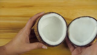 Closeup of woman hands opening a rough brown shell of a tropical fruit coconut