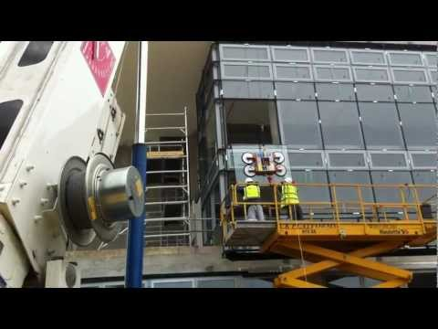 Trailer crane installing curtain wall glazing