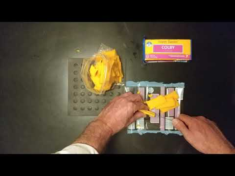 TIME LAPSE VIDEO CUTTING HALF POUND BLOCK OF COLBY CHEESE WITH SERRATED KNIFE
