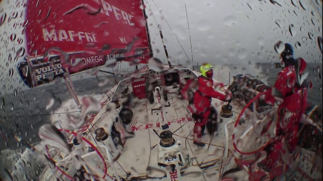 "Crash cam from the stern as MAPFRE surfs in big wind. Suddenly Blair, on the helm, points forward: ""Whale! Big whale!"" Neti jumps up to look, and they pass the whale, which surfaces a half a boatlength to starboard as they surf past. Someone (sounds like Tamara) shouts a greeting to it. Ridiculous!"