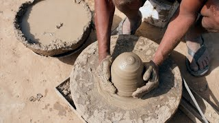 A potter working on potter's wheel and giving shapes to the mud clay
