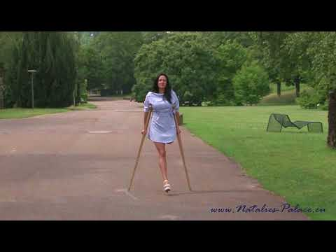Amputee model Natalie is in a park with wooden crutches