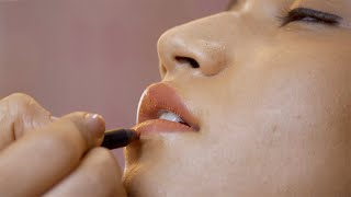 Hands of a makeup artist painting lips of a model with nude shade lipstick