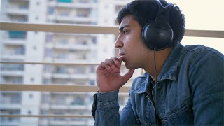 Young handsome man listening to music using his headphones - technology concept