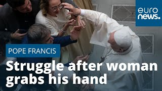 Pope Francis struggles free after woman grabs his hand outside Vatican