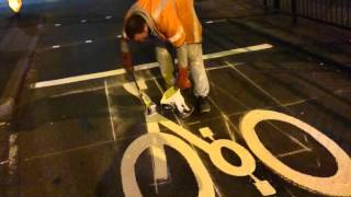 Expert road painters putting in a bike symbol