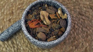 The mixture of Indian raw spices in a vintage traditional grinding stone