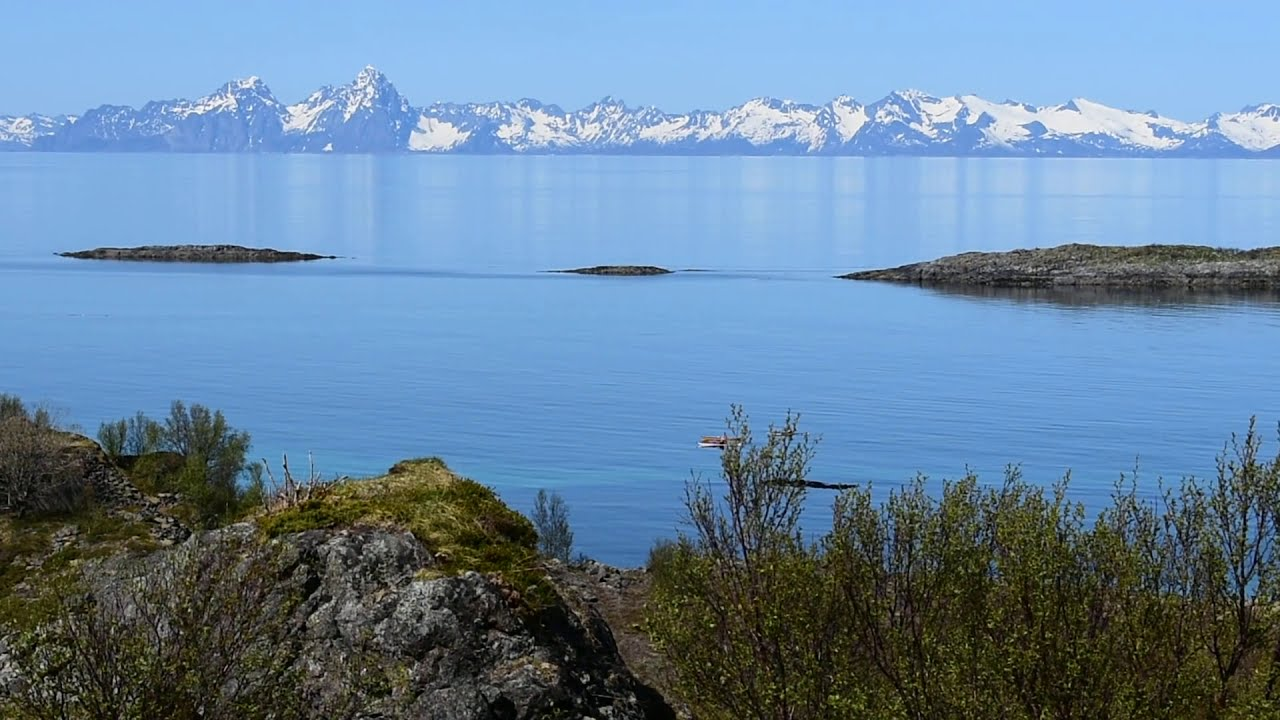 Kayakers in West fjord between Battery Dietl & Lofoten wall of mountains a sunny summer day. Slow Tv