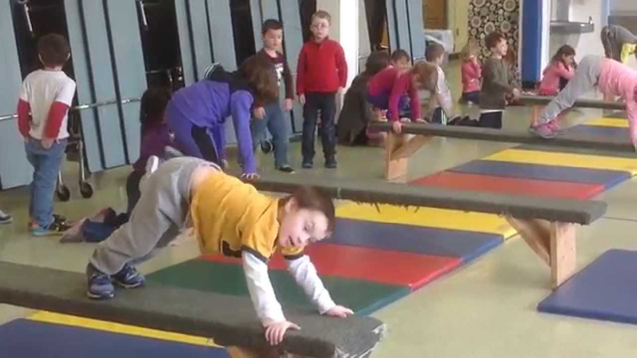 Elementary Kids Travel And Do Balance Stunts On Gymnastic