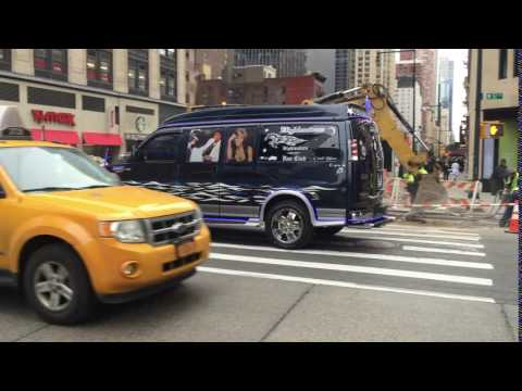 """""""COOL BLUE"""" VAN CRUISING BY ON WEST 57TH STREET IN THE MIDTOWN AREA OF MANHATTAN IN NEW YORK CITY."""