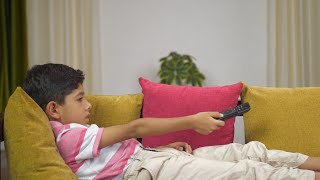 Lazy Indian boy lying on a couch and watching TV - lifestyle kids