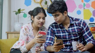 Young Indian couple sitting on the sofa and watching their smartphones