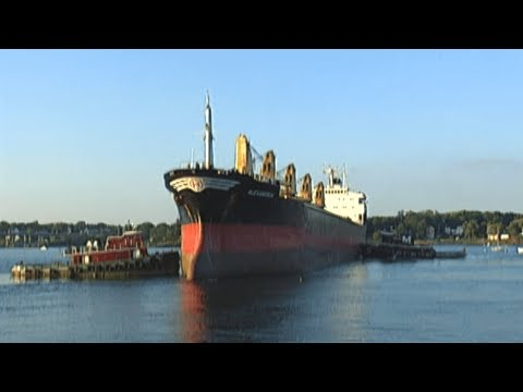 Big Tug Boats Push A Giant Ship Into Harbor Where Coal Is Unloaded