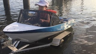 Two year old drives his own mini petrol powered speed boat.